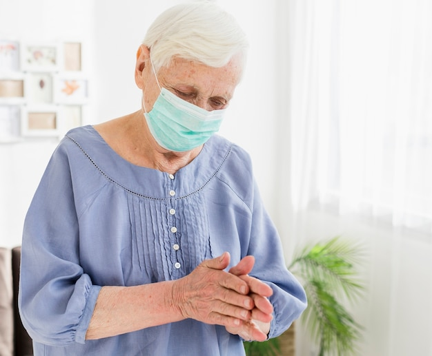 Mujer mayor con máscara médica rezando en casa