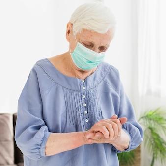 Mujer mayor con máscara médica rezando
