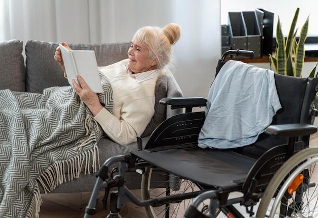Mujer mayor, mentira en cama, al lado de, un, silla de ruedas