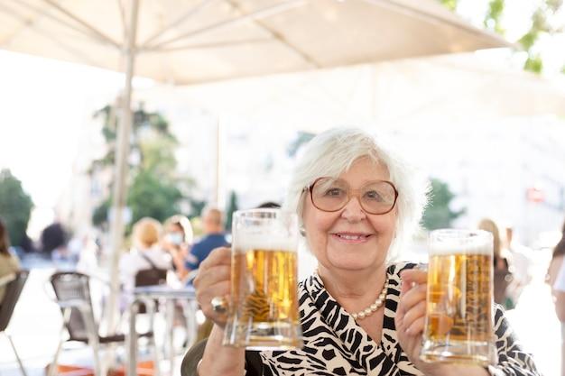 Mujer mayor mirando a la cámara sentado en una terraza bebiendo cerveza. mujer con dos cervezas en la mano