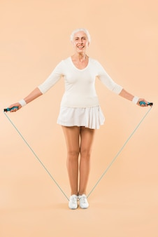 Mujer mayor moderna con cuerda de saltar