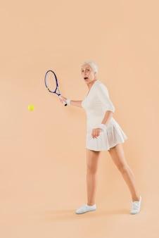 Mujer mayor moderna jugando al tenis