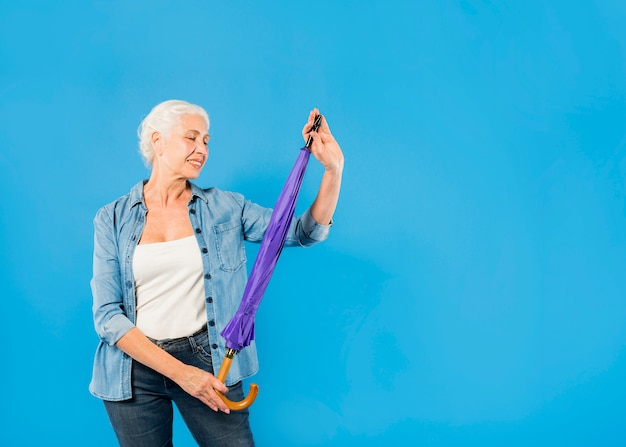 Mujer mayor moderna con paraguas