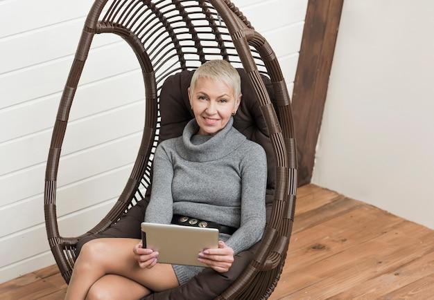 Mujer mayor moderna que sostiene una tableta