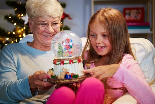 Mujer mayor con nieta sosteniendo una decoración navideña