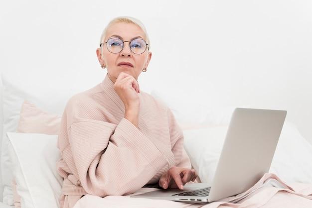 Mujer mayor pensativa que presenta en cama con la computadora portátil