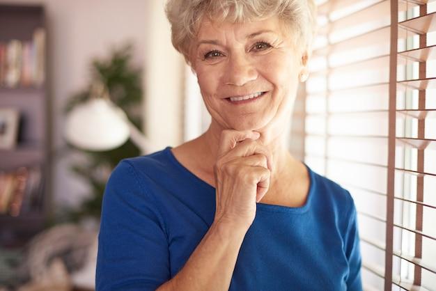 Mujer mayor, posición, al lado de la ventana