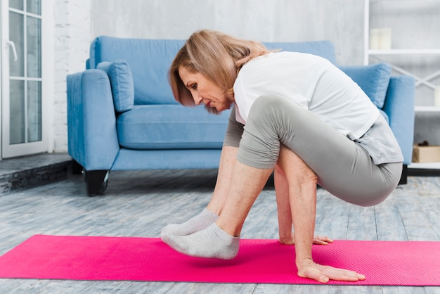 Mujer mayor practicando yoga en casa