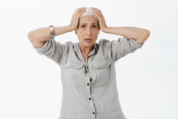 Mujer mayor preocupada y preocupada entrando en pánico, agarrando la cabeza y luciendo angustiada