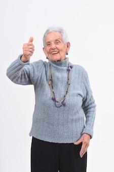 Mujer mayor con los pulgares hacia arriba y sonríe sobre fondo blanco