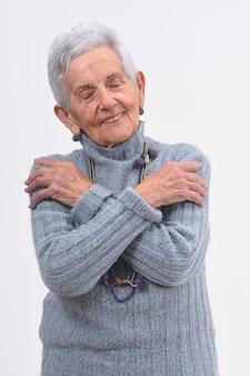 Mujer mayor que abraza en el fondo blanco