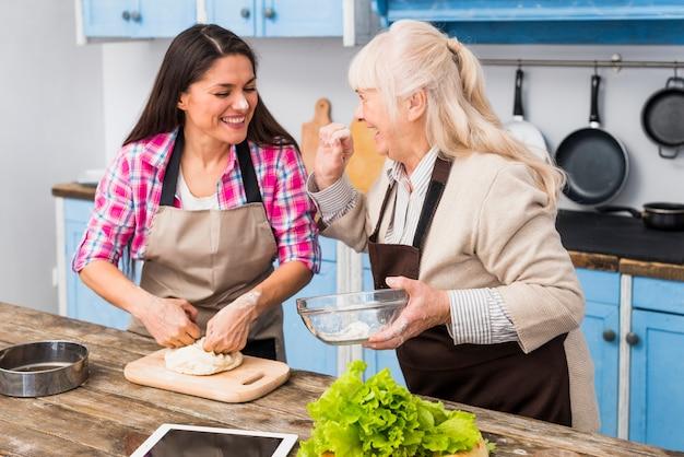 Mujer mayor que aplica harina sobre la cara de la hija joven que prepara la comida en la cocina