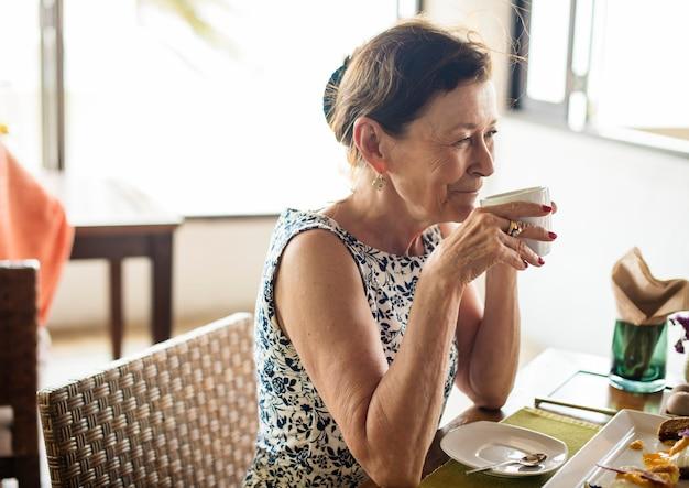 Mujer mayor que bebe una taza de café