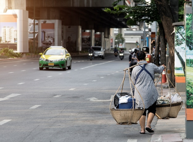 Una mujer mayor que come una cesta de comida se vende en la calle