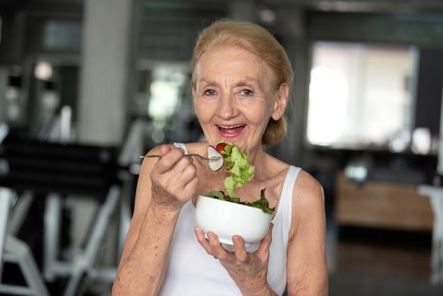 Mujer mayor que come la ensalada sana. concepto de estilo de vida de salud de ancianos.