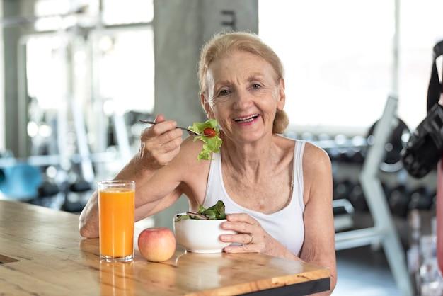 Mujer mayor que come la ensalada sana y el zumo de naranja. concepto de estilo de vida de salud de ancianos.