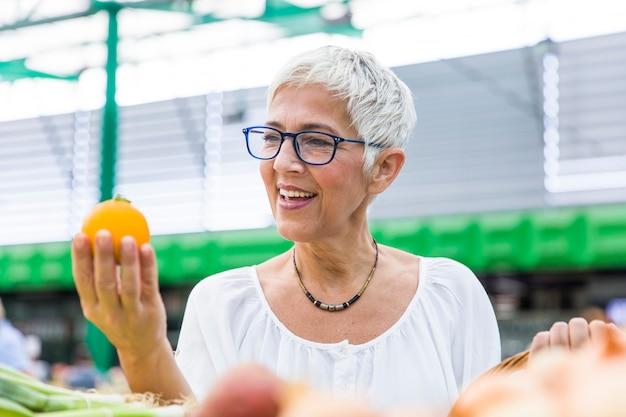 Mujer mayor que compra cebolla en mercado