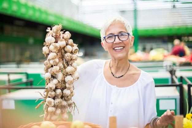 Mujer mayor que compra la porción de ajo en mercado