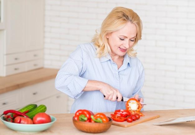 Mujer mayor que corta las rebanadas de paprika rojo con el cuchillo en tajadera en la cocina