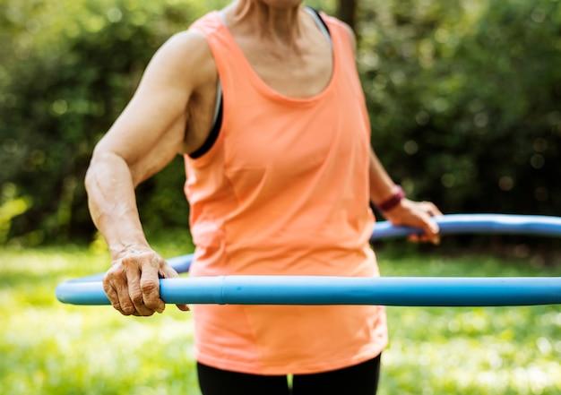 Mujer mayor que ejercita con un aro de hula
