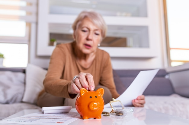 Mujer mayor que hace finanzas en casa. mujer mayor con la calculadora y contando el dinero euro en casa. concepto de negocio, ahorro, anualidad, edad y personas