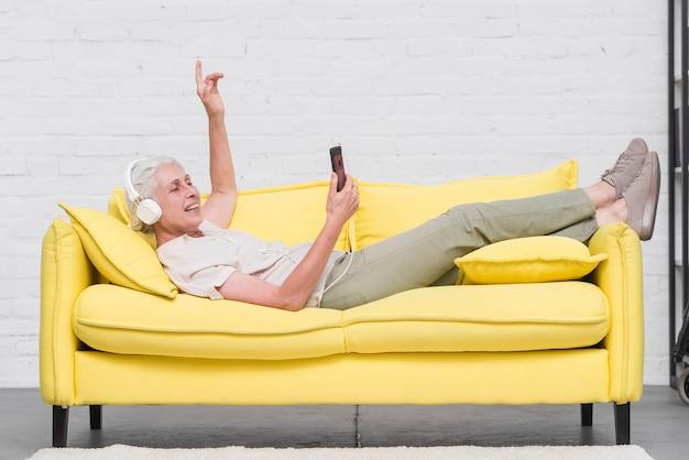 Mujer mayor que miente en el sofá amarillo que disfruta de la música en el móvil a través del auricular