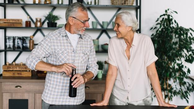 Mujer mayor que mira al marido que abre la botella de cerveza en la cocina