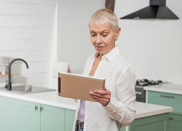 Mujer mayor que mira en su tableta en la cocina