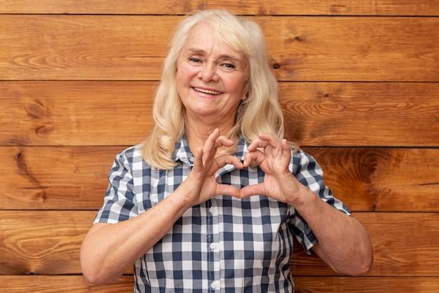 Mujer mayor que muestra forma del corazón con las manos