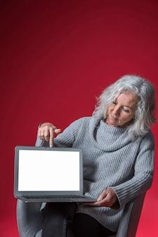 Mujer mayor que se sienta en la butaca que señala su dedo en una computadora portátil abierta
