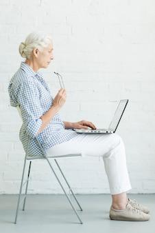 Mujer mayor que se sienta en silla usando la computadora portátil