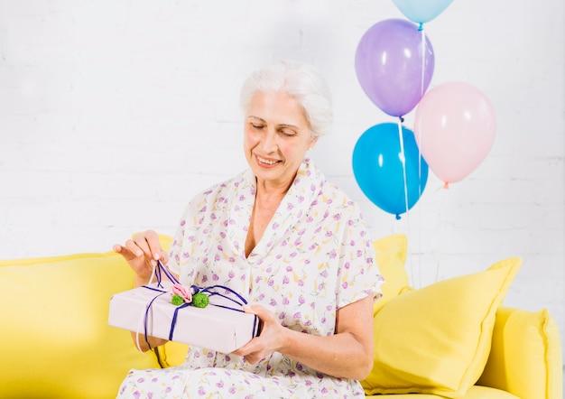 Mujer mayor que se sienta en el sofá que desempaqueta el regalo de cumpleaños