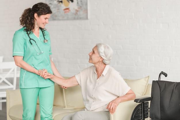 Mujer mayor que se sienta en el sofá que lleva a cabo la mano de la enfermera