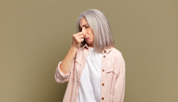 Mujer mayor que se siente disgustada, tapándose la nariz para evitar oler un hedor desagradable y desagradable