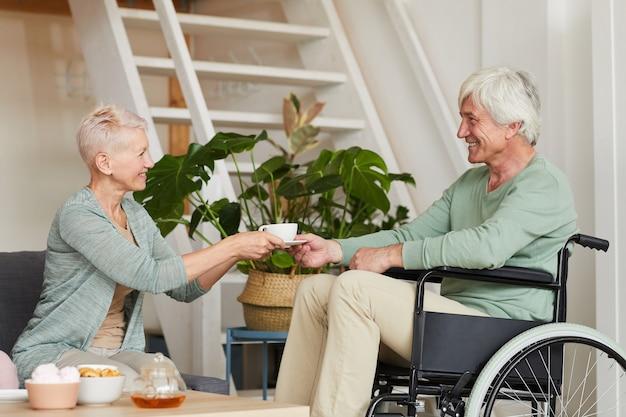 Mujer mayor que sirve la taza de té a su marido discapacitado en silla de ruedas en la habitación