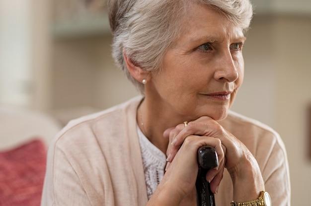 Mujer mayor que sostiene el bastón