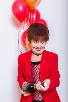 Mujer mayor que sostiene una botella de champán en un fondo blanco