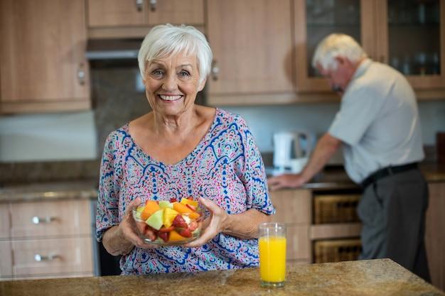 Mujer mayor que sostiene el cuenco de fruta mientras el hombre trabaja en la cocina de casa