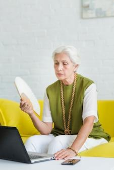Una mujer mayor que sostiene la fan que mira la computadora portátil