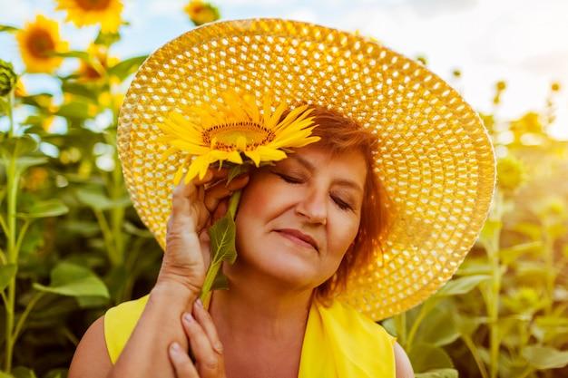 Mujer mayor que sostiene el girasol en campo del verano que disfruta de la naturaleza. mujer feliz relajarse al aire libre.