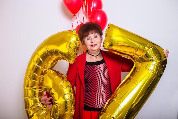 Mujer mayor que sostiene globos de la fiesta de cumpleaños en un fondo blanco
