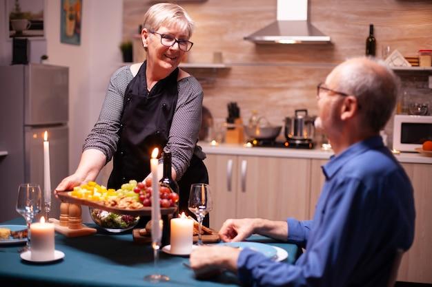 Mujer mayor que sostiene la placa de madera con y mirando al marido durante la cena festiva. pareja de ancianos hablando, sentados a la mesa en la cocina, disfrutando de la comida, celebrando su aniversario.