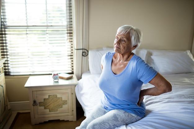 Mujer mayor que sufre de dolor de espalda en el dormitorio en casa