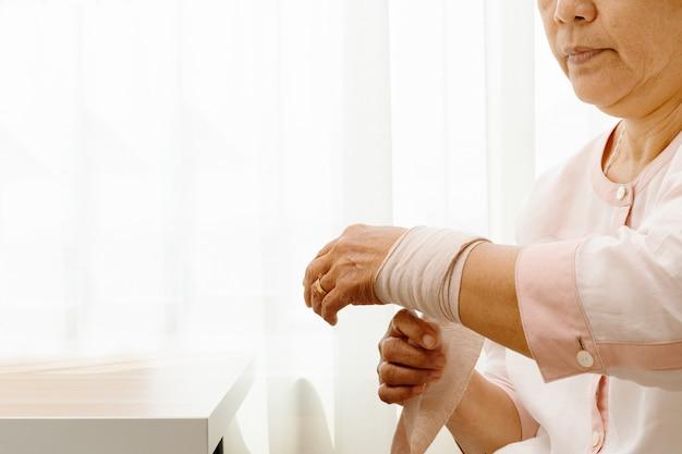 Mujer mayor que sufre de dolor en la mano de la muñeca, concepto de problema de salud