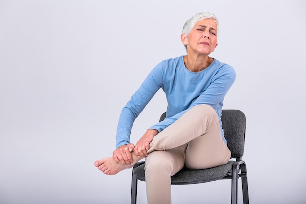Mujer mayor que sufre de dolor en la pierna en casa.