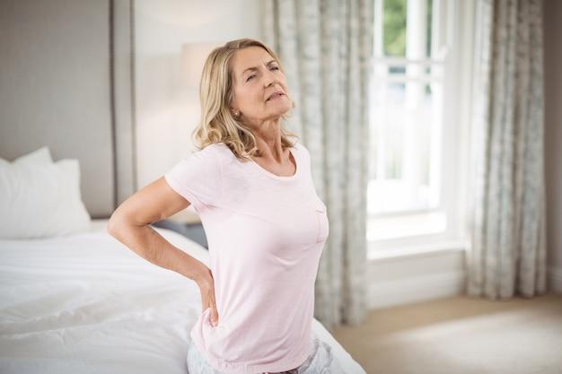 Mujer mayor que tiene dolor de espalda en dormitorio