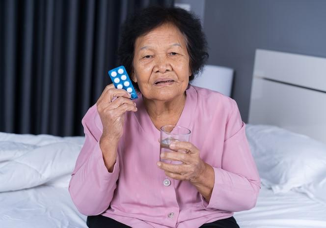 Mujer mayor que toma la píldora con un vaso de agua en la cama
