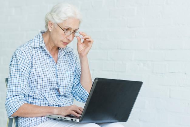 Mujer mayor que usa la computadora portátil contra la pared blanca