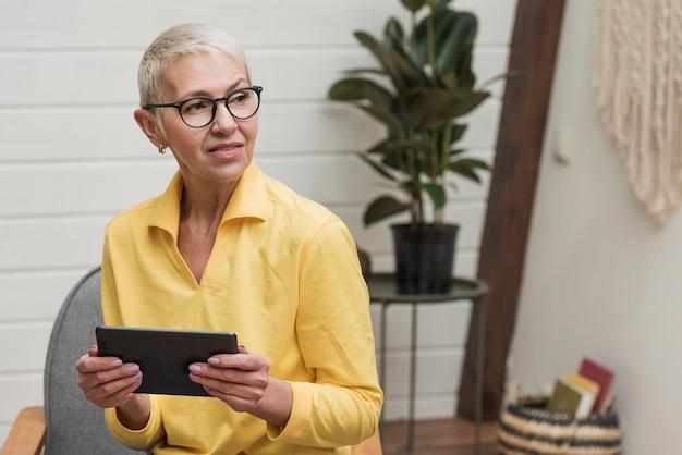 Mujer mayor que usa una tableta mientras mira lejos