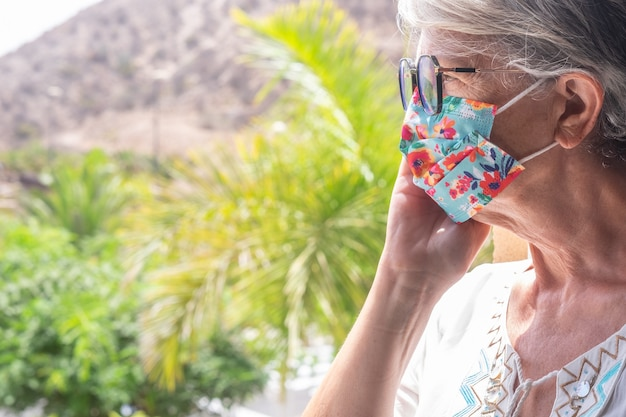 Mujer mayor quedarse en casa en la ventana para covid cuarentena, mirando hacia afuera